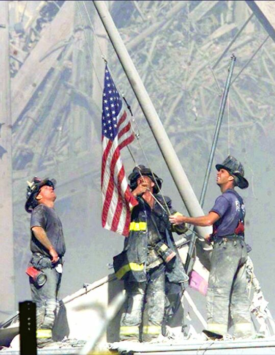 Image of firefighters raising the flag at Ground Zero on 9/11/2001.